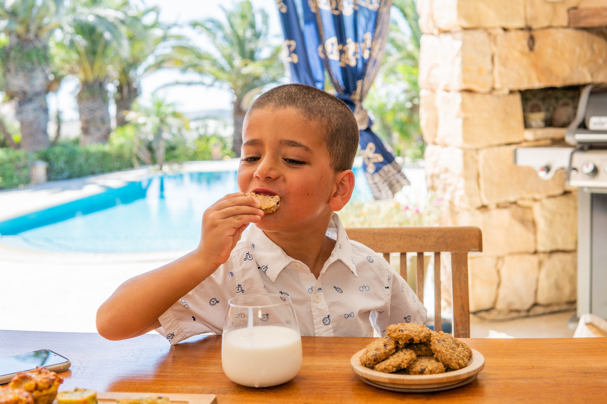 toddler eating oaty chocolate chop cookies with milk